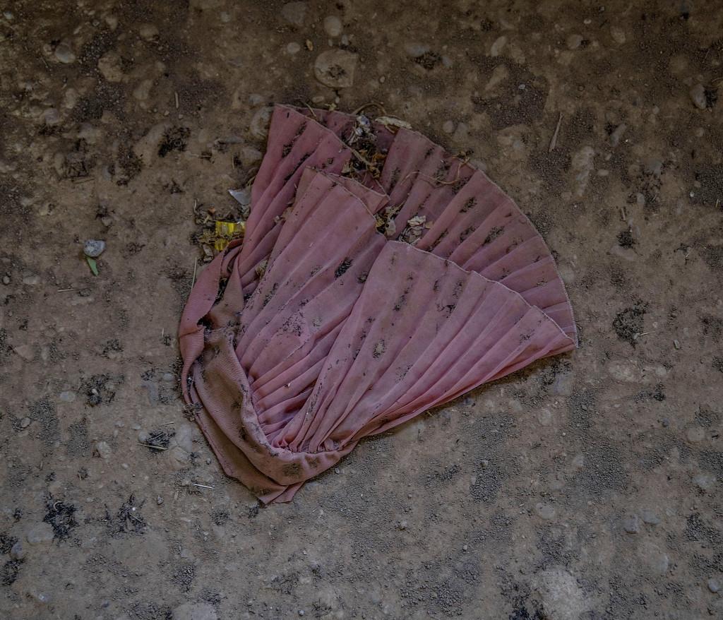 En rosa klänning ligger slängd på golvet i ett av IS-husen i byn Shaquli söder om Mosul. Foto: Magnus Wennman