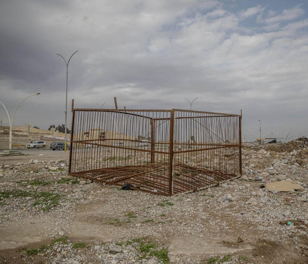 Adnan Tahar visar platser där is avrättade människor i östra Mosul. En stålbur står uppställd nedanför en stor läktare, där brukade IS bränna eller skjuta människor som de ansåg gjort något fel. Foto: Magnus Wennman