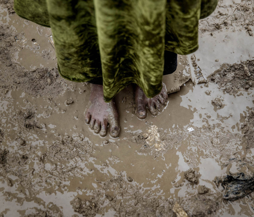 Flyktinglägret Hammam al-alil söder om Mosul. Hit anländer tusentals människor från de befriade delarna av västra Mosul. Det är lera överallt. En ung flicka anländer till lägret utan skor på fötterna. Foto: Magnus Wennman